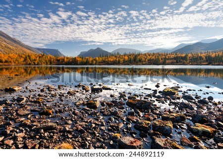 Iconic Hibiny mountains landscape with cloudy evening sky and bright colorful taiga forest reflected in shallow Polygonal lake, Russia above the Arctic circle - stock photo