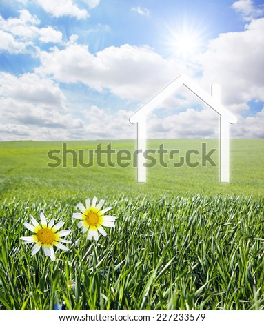 Iconic symbol of a house on a green landscape - stock photo