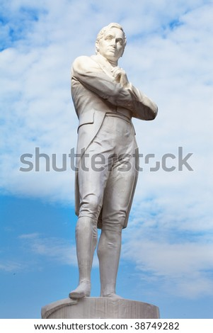 Iconic tourism landmark symbol of Singapore, Sir Stamford Raffles Statue with dramatic lighting at Boat Quay with blue skies