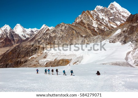 Iconic View of high Altitude Himalaya Mountains and group of Climbers walking up on snowy Glacier