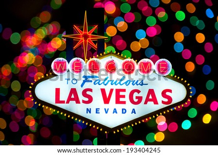 Iconic Welcome to Fabulous Las Vegas sign with multiple blurry lights in the back  - stock photo