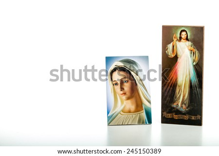 Icons  of Merciful Jesus and Our Lady of Medjugorje, the Blessed Virgin Mary isolated on white background with matte reflection on white table. - stock photo