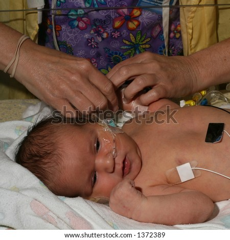 ICU nurse tending to a sick infant - stock photo