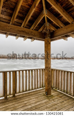 Icy frozen lake from the deck of a wooden gazebo - stock photo