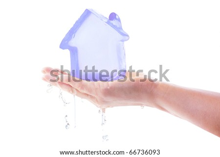 Icy house model melts on hand and turns into water drops - stock photo