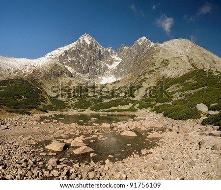 Icy lake with rocks, beautiful cirrocumuluses and high mountains. Slovakian Lomnica in High Tatra Mountains. - stock photo