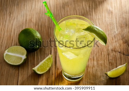 Icy lime cocktail on a wooden table. Halves of a lime surrounding the glass with a drink. Brown and green combination of colors. - stock photo