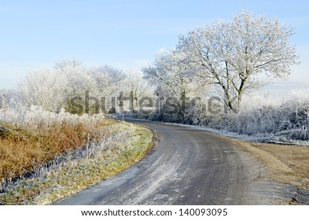 Icy morning on country road after hard hoar frost - stock photo