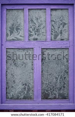 Icy pattern on frozen old wooden window with purple frame. - stock photo