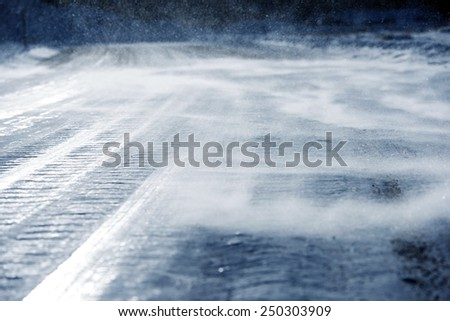 Icy Road with Drifting Snow Closeup. Dangerous Icy Road Conditions. - stock photo