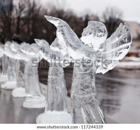 Icy sculpture of frozen angel in winter city - stock photo