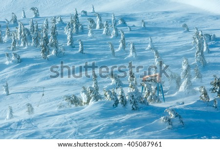 Icy snowy fir trees and ski lift on winter morning hill. - stock photo