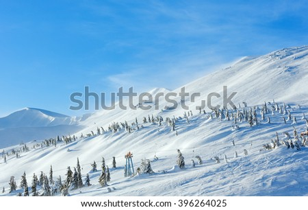Icy snowy fir trees and ski lift on winter morning hill (Carpathian). - stock photo