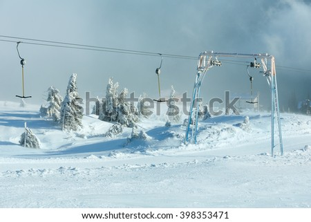 Icy snowy fir trees and surface lift on winter morning hill. - stock photo