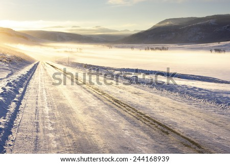 Icy winter road in the morning light in Yellowstone National Park. - stock photo