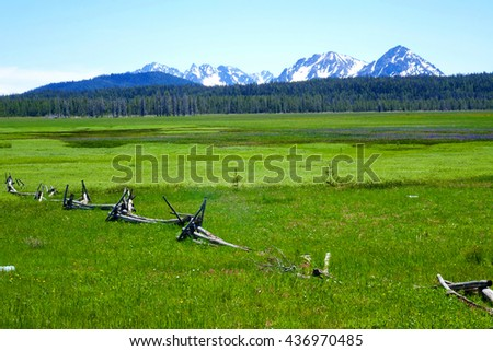 Idaho's Sawtooth mountains provide a beautiful background for a high elevation meadow. A crooked rail fence in the foreground has fallen into disrepair.                                - stock photo