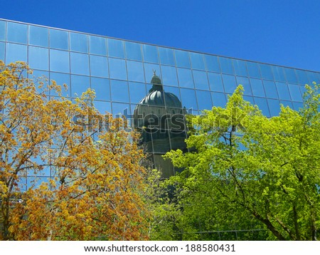 Idaho's state capitol (built 1905-1912) is reflected in the mirrored surface of the building across the street (constructed in the 1970s.) - stock photo