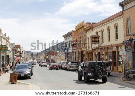Idaho Springs, CO, USA - April 19, 2014: A sunny, commercial area of Miner Street where a lot of stores and shopping happens.Many people, vehicles and merchants line the downtown shopping area. - stock photo