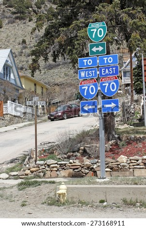 Idaho Springs, CO, USA - April 19, 2014: Business Loop 70 West and East Interstate 70 direction signs along Colorado Boulevard at 13th Avenue in Idaho Springs Colorado. East / West Interstate 70 signs - stock photo
