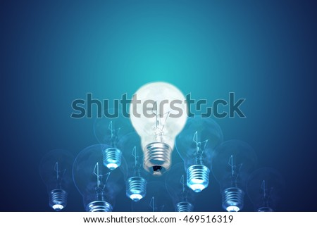 Idea and leadership concept incandescent edison type bulbs on blue background