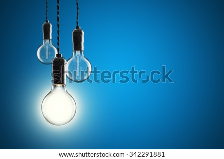 Idea and leadership concept Vintage incandescent Edison type bulbs on color wall - stock photo