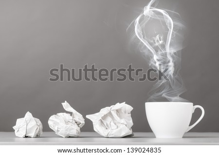 idea birth. crumpled wads and bulb silhouette on gray - stock photo