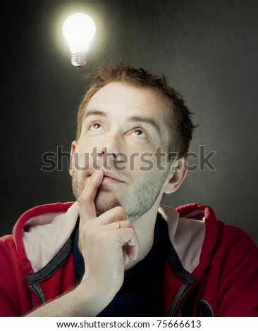 Idea Bulb above young man's head - stock photo
