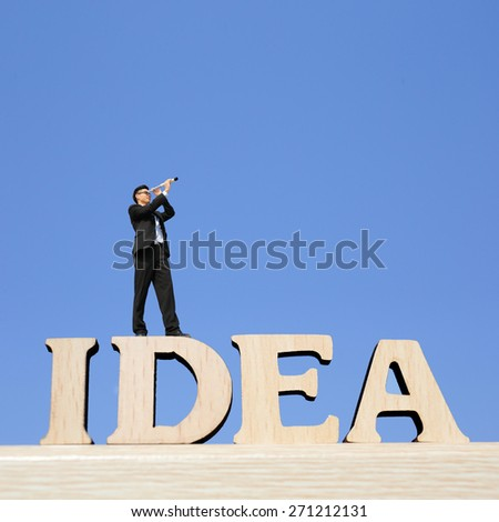 Idea - business man stand on Idea text word with telescope ( spyglass ) looking forward, great for your design and business concept - stock photo