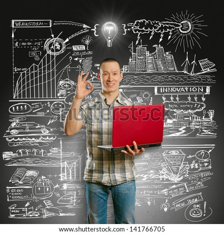 Idea concept. Asian male with laptop in his hands shows OK, with lamp above his head - stock photo