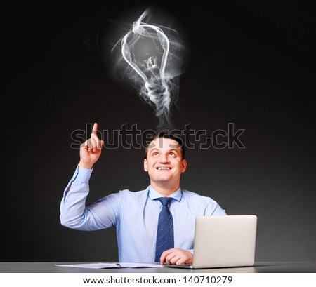idea concept. businessman is sitting at his table with laptop - stock photo