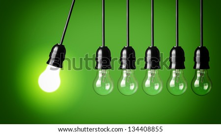 Idea concept on green background. Perpetual motion with light bulbs - stock photo