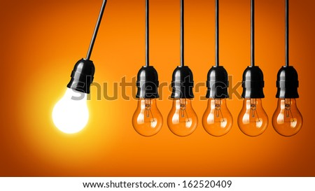 Idea concept on orange background. Perpetual motion with light bulbs - stock photo
