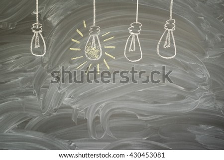 idea concept - row of light bulbs with glowing one on blackboard with copy space - stock photo