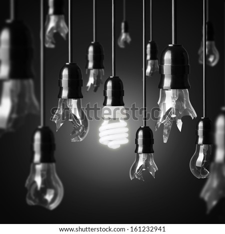 idea concept with broken bulbs and one glowing energy saving bulb - stock photo