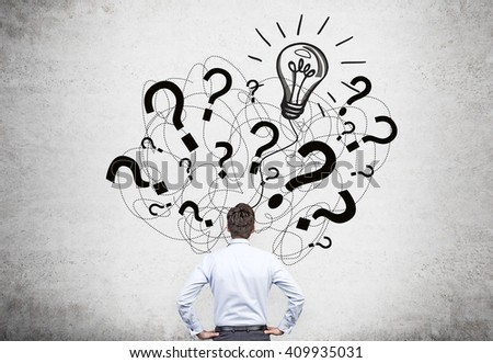 Idea concept with businessman facing question mark and bulb sketch on concrete wall - stock photo