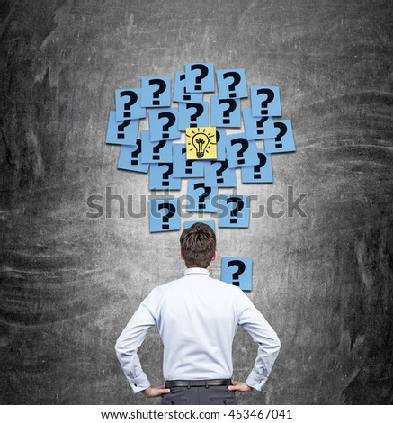 Idea concept with businessman looking at chalkboard wall with abstract sticker light bulb and question marks. Back view - stock photo