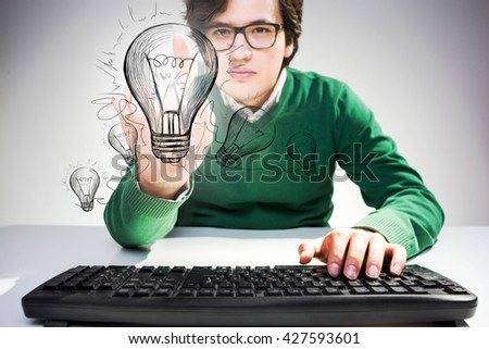 Idea concept with concentrated young man sitting at desk with keyboard and pointing at abstract lightbulb sketch - stock photo