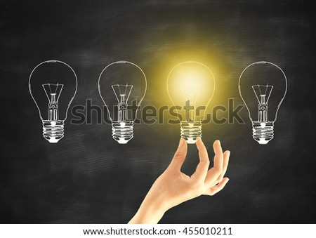 Idea concept with female hand holding abstract illuminated light bulb on chalkboard background - stock photo