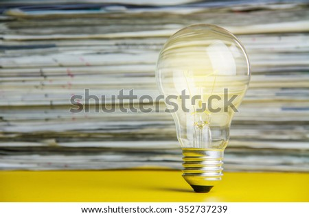 idea concept with light bulbs and newspaper. - stock photo