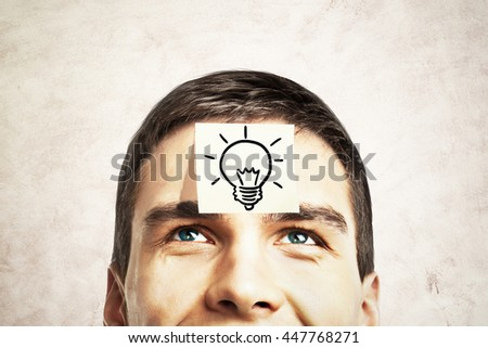 Idea concept with lightbulb sketch drawn on sticker glued to happy guy's forehead on concrete background - stock photo