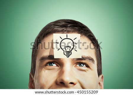 Idea concept with lightbulb sketch drawn on sticker glued to happy guy's forehead on green background - stock photo