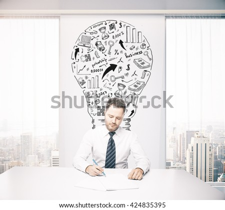Idea concept with lightbulb sketch on wall in office with young handsome businessman sitting at desk and working - stock photo