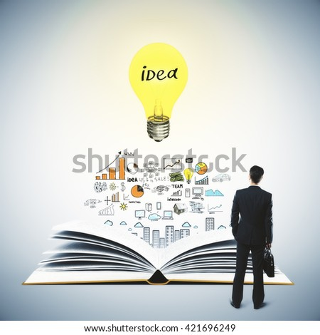 Idea concept with thinking businessman, book, light bulb and business sketch on grey background - stock photo