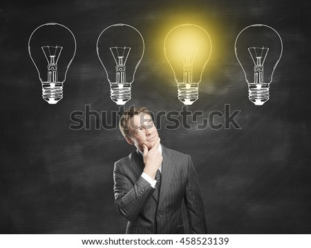 Idea concept with thoughtful businessman standing against chalkboard with illuminated drawn light bulbs