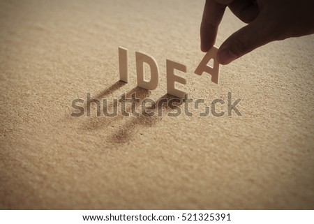 IDEA wood word on compressed board,cork board with human's finger at A letter