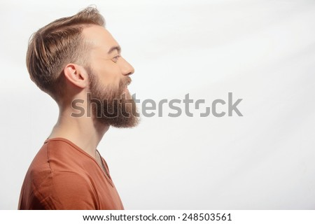 Ideal beard. Side view portrait of handsome bearded man wearing orange tshirt and smiling at copy space while standing against white background - stock photo