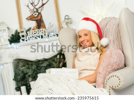 Ideal Christmas and New Year. Young and beautiful girl is sitting in festive Christmas decorated living room and smiling. She is wearing Santa Claus hat and sitting near fire place - stock photo