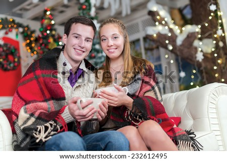 Ideal warm Christmas. Young and beautiful pair is sitting on the sofa in festive New Year living room. Both are holding cups with New Year cacao and having festive fun - stock photo