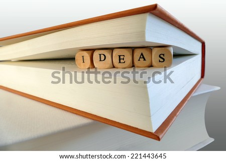 Ideas message written with wooden blocks between book pages, symbol, concept - stock photo