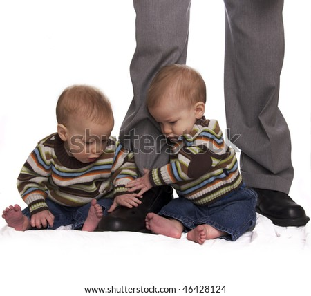 Identical twin baby boys holding onto the their daddy's legs for support